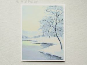 note card printed with a painting of a winter landscape showing trees and snow beside a lake, displayed on a light gray background