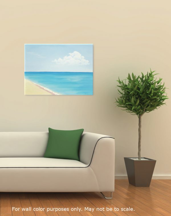 Seascape painting of a sandy beach with a calm blue ocean and a blue sky, displayed in a room with neutral wall color, a white sofa, and a hardwood floor.