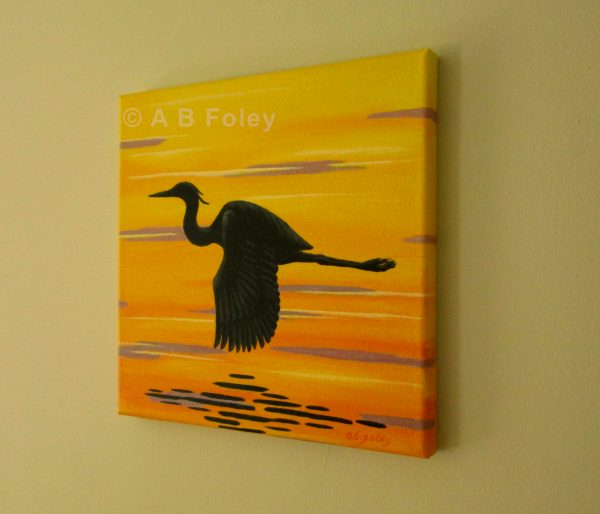 painting on canvas of a great blue heron silhouette flying over sunset water in yellow and orange with purple ripples, viewed from the right