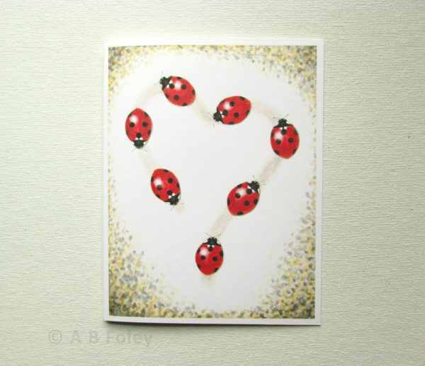 printed watercolor art note card with image of seven realistic ladybugs walking a heart shaped path, photographed on a white background