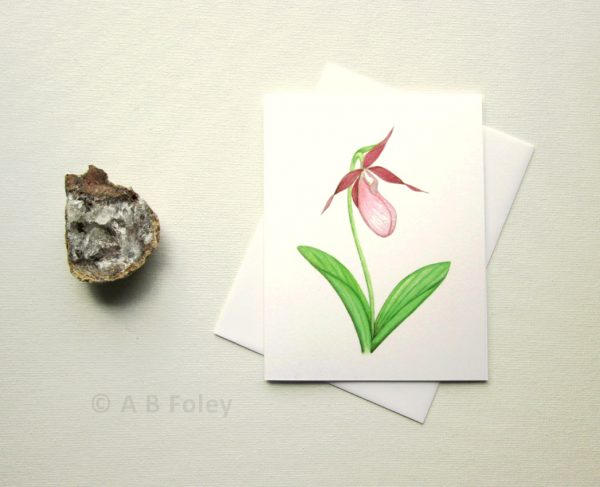 watercolor art note card of pink lady's slipper orchid, pictured with a white envelope and geode on a white background