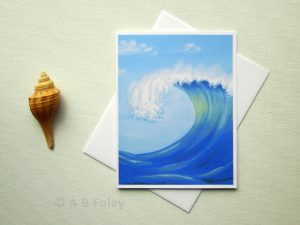 note card with a painting of a blue ocean wave topped with white foam, viewed on a white background with a white envelope, next to a tan seashell