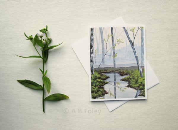 nature art note card showing a misty gray forest with grey trees, green grass and water, displayed on a white background with a white envelope and a plant