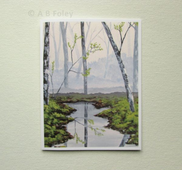 nature art note card showing a misty gray forest with grey trees, green grass and water, displayed on a white background