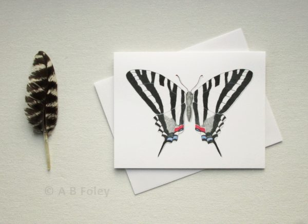 watercolor butterfly art note card of zebra swallowtail butterfly with envelope and feather, viewed on a light gray background