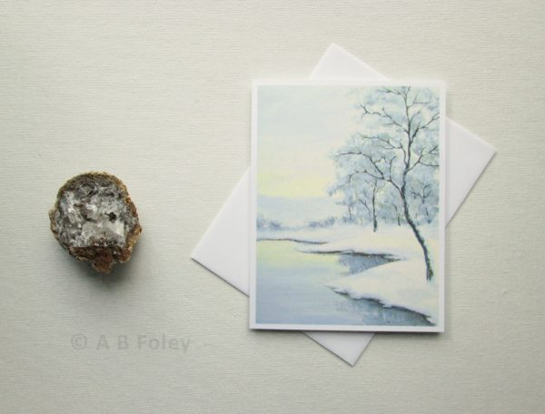 note card printed with a painting of a winter landscape showing trees and snow beside a lake, displayed on a light gray background with an envelope and geode